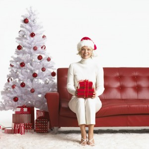 Young Woman Sitting on Couch Holding Christmas Present and Wearing Santa Hat